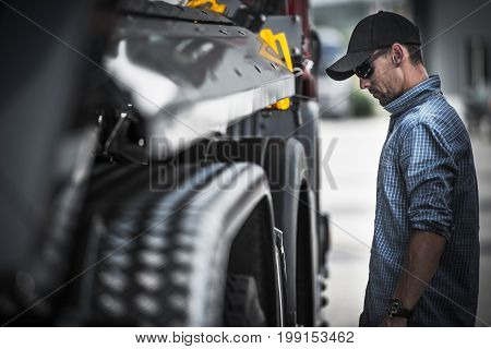 Truck Driver Load Check. Caucasian Semi Truck Driver Checking on His Vehicle and the Load.