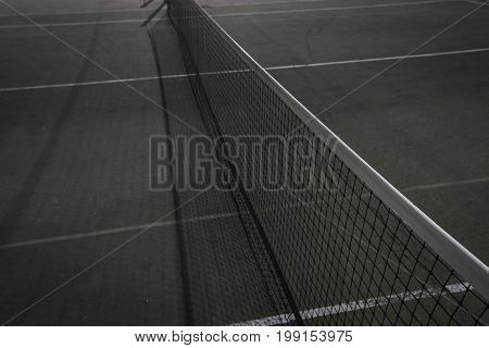 Green and blue tennis court with net and shadow