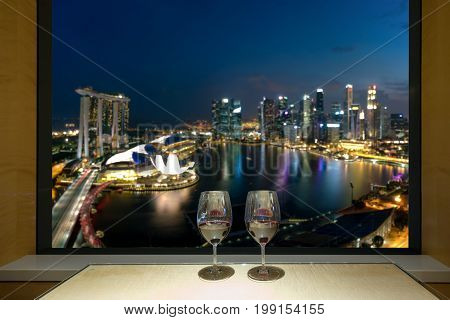 Closeup of a glasses of red wine at windowsill against night Singapore city view of urban city sky line blurring lights. Singapore.