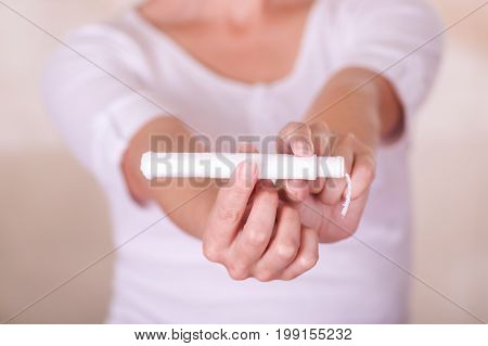 Close up of a young woman pointing in front of her a menstruation cotton tampon and manipulating the tampon, in a blurred background.