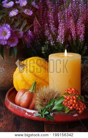 Autumn thanksgiving decor with candle flowers and pumpkin