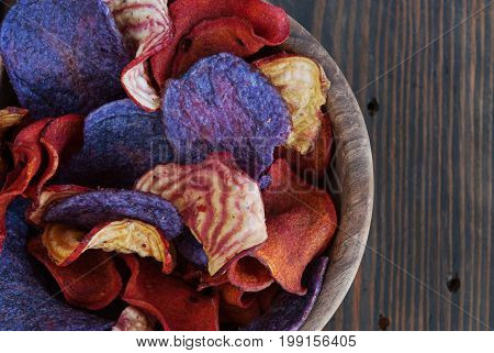 Crunchy organic potatoes blue potatoes chips and beetroot chips served as a finger food snack in a wooden bowl