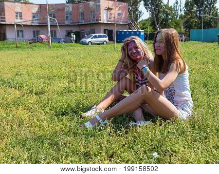 Odessa, Ukraine - August 5, 2017: Two Girls Sprinkled Each Other With Colored Powders, Sit And Relax