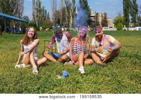 Odessa, Ukraine - August 5, 2017: Young People Sprinkled Each Other With Colored Powder Sit On Lawn,