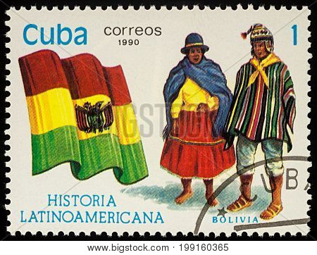 Moscow Russia - August 09 2017: A stamp printed in Cuba shows national flag and a couple in Bolivian traditional costumes series