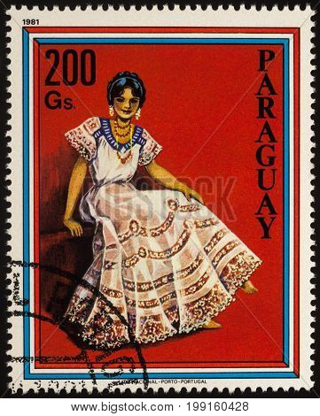 Moscow Russia - August 09 2017: A stamp printed in Paraguay shows sitting beautiful young woman in Paraguayan traditional dress series