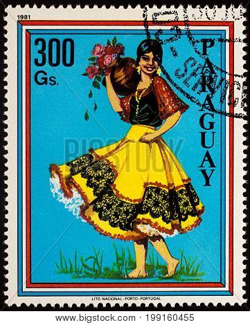 Moscow Russia - August 09 2017: A stamp printed in Paraguay shows beautiful young woman in Paraguayan traditional dress with flowers series