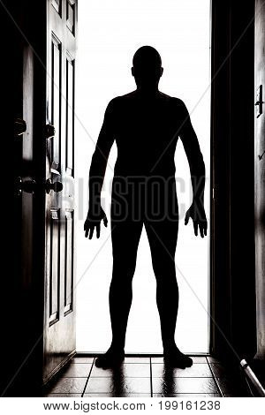 Naked man at doorway threshold in silhouette white background