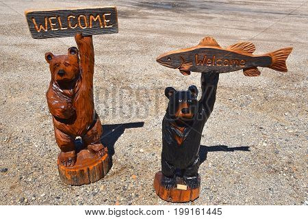 Several carved bears  from a chainsaw are holding signs with a WELCOME greeting