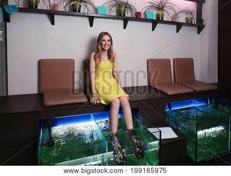 Young woman in beauty salon. Fish pedicure as new modern spa treatment