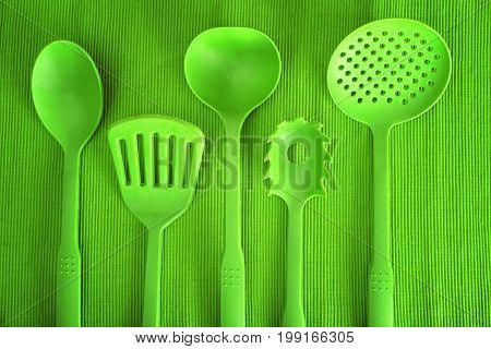 Green utensils on textured background