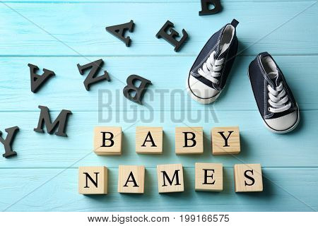 Wooden cubes with text BABY NAMES and shoes on color background