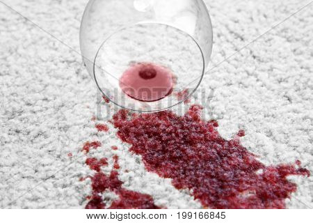Glass of red wine spilled on white carpet, close up