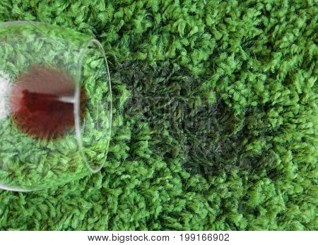 Glass of red wine spilled on green carpet, close up