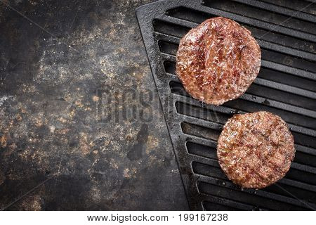 homemade grilled hamburger on the cast iron BBQ grate in rustic vintage style with copy space
