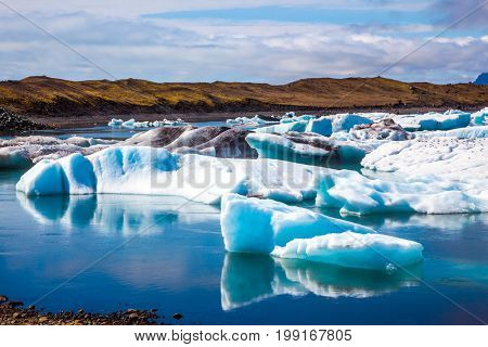 Drift ice Ice Lagoon - Jokulsarlon. The unique nature of Iceland. Icebergs and ice floes are reflected in the smooth water surface. The concept of extreme northern tourism