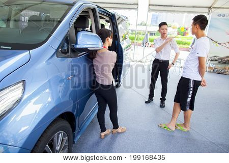 Dongguan, Guangdong, China - August 7, 2017: Car salesperson talking with prospective Chinese brand automobile buyer at Dongguan car exhibition in front of large van