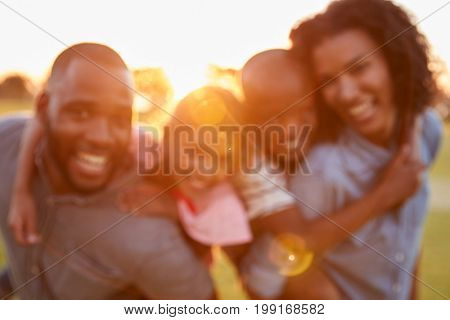 Portrait of young black couple with children on piggyback
