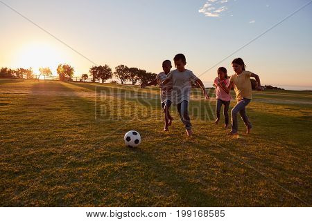 Four children chasing a ball during a game in a field