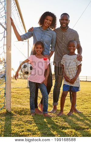 Portrait of a young black family next to a football goal