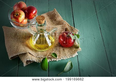Red apples in vase and apple cider vinegar on wooden table. Concept - healthy food from your garden. Top view. Copy space.