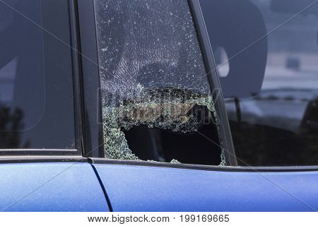 Smashed auto door window from vehicle burglary.
