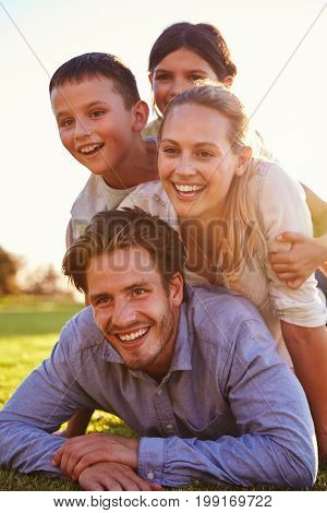Piled up happy white family lying on grass looking away