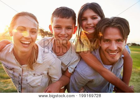 Young couple piggybacking their kids outdoors look to camera