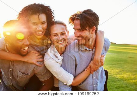 Two happy couples piggyback outdoors looking at each other