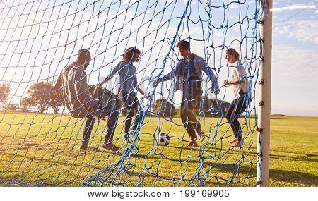 Two couples enjoy a game of football, seen through goal net