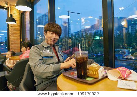 BUSAN, SOUTH KOREA - CIRCA MAY, 2017: man eat at McDonald's restaurant. McDonald's is an American hamburger and fast food restaurant chain.