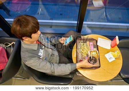 BUSAN, SOUTH KOREA - CIRCA MAY, 2017: man at McDonald's restaurant. McDonald's is an American hamburger and fast food restaurant chain.