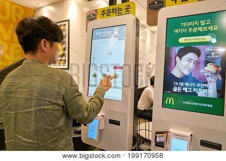 BUSAN, SOUTH KOREA - CIRCA MAY, 2017: man use ordering kiosk at McDonald's restaurant. McDonald's is an American hamburger and fast food restaurant chain.