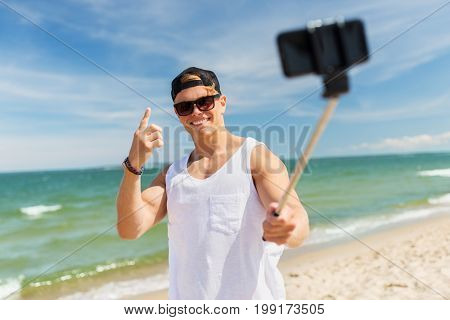summer holidays and people concept - happy smiling young man with smartphone selfie stick taking picture on beach