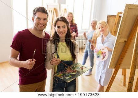 creativity, education and people concept - group of artists or students with brushes and palettes painting on easels at art school studio