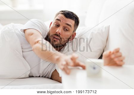 morning and people concept - sleepy young man in bed reaching for alarm clock at home