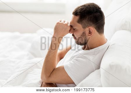 people, bedtime and rest concept - stressed man in bed at home