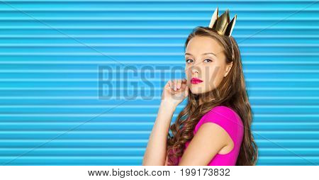 people, holidays and fashion concept - young woman or teen girl in pink dress and princess crown over blue ribbed background