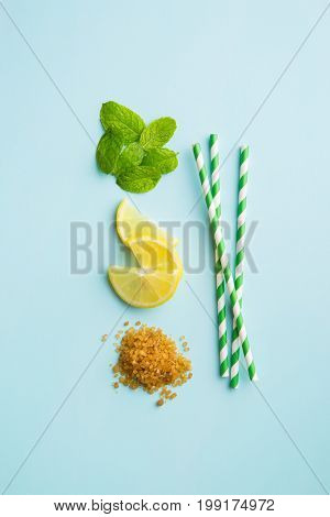 Mojito ingredients. Lemon, mint and cane sugar blue background. Sweet sugar, mint leaves, lemon and striped straw.