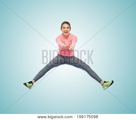 sport, fitness, motion and people concept - happy smiling young woman jumping in air over white background showing thumbs up