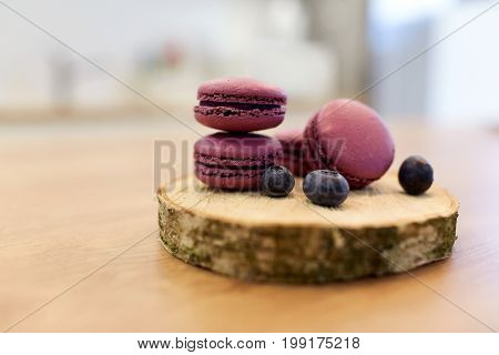 cooking, confectionery and baking concept - blueberry macarons on wooden stand