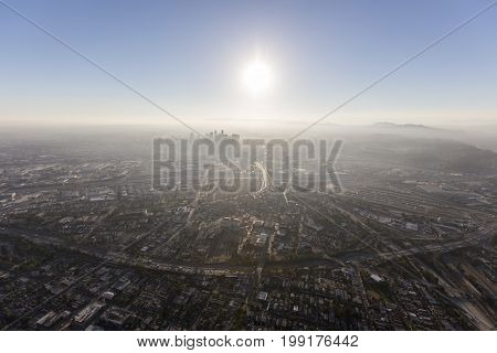 Smoggy summer afternoon aerial view of urban Los Angeles streets and towers in Southern California.