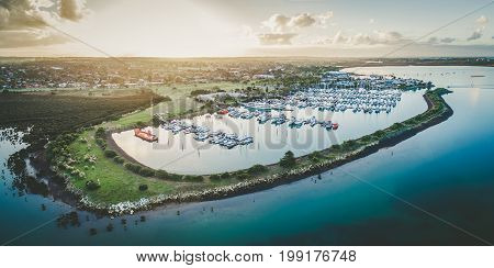 Aerial view of Westernport Marina with moored boats and Hastings coastline at beautiful sunset. Melbourne Victoria Australia