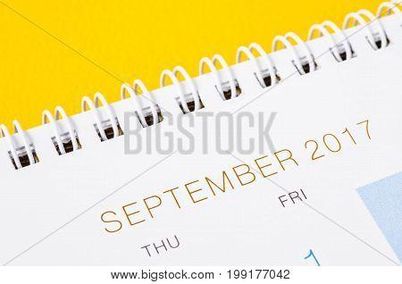 September on white calendar page desk calendar on yellow background