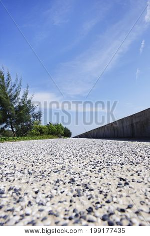long stone road in a beach with cloudy blue sky, trees and stonewalled background at sweet beach (pantai manis) papar , sabah , malaysia