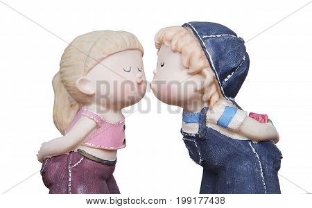 A full of love porcelain little boy wearing jeans cap and overalls doll about to kiss a cute and lovely little porcelain girl wearing a pink bare midriff doll in a white background