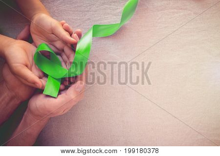 Adult And Child Hands Holding Lime Greenribbon, Toning Background, Mental Health Awareness And Lymph