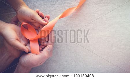 Adult And Child Hands Holding Orange Ribbons,  Leukemia Cancer Awareness And Multiple Sclerosis Awar