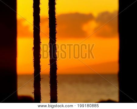 Nautical ropes in front of spectacular orange sunset in Hawaii at sea.