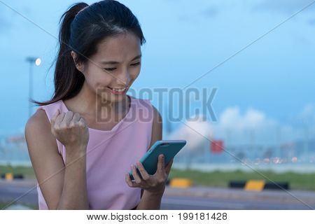 Woman get the air ticket on smart phone in airplane track at the evening
